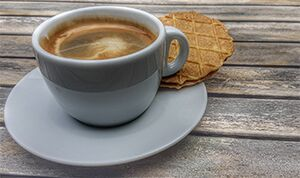 Photo of a cup of espresso on a saucer with a cookie on wooden slats