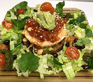 Photo of a black bean burger stack surrounded by salad