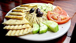 photo of hummus, pita bread, and vegetables on a white plate