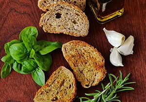 Top down photo of slices of bread beside herbs