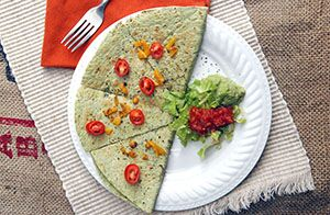 Top down image of a spinach quesadilla, sliced topped with cherry tomatoes on a white plate